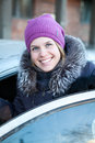 Pretty smiling woman getting into new car Stock Images