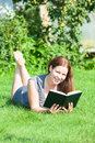 Pretty smiling woman lying on lawn with book in hand and looking at camera Royalty Free Stock Images