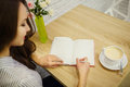 Pretty smiling woman makes entry in her diary on table Royalty Free Stock Photo