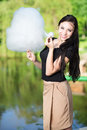 Pretty smiling woman posing with a cotton candy near the pond Royalty Free Stock Images