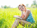 Pretty smiling woman reads the book at nature young Royalty Free Stock Photo