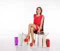Pretty smiling woman with shopping bags young in red dress and shoes sitting on the chair Royalty Free Stock Photography