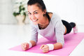 Picture : Pretty smiling young woman doing plank abdominal muscles pain