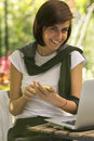 Pretty smilling young woman using a smartphone and laptop beautiful smiling wearing white t shirt smart phone sitting at table Royalty Free Stock Image