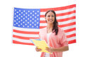 Pretty student smiling holding notebooks against american flag Stock Photography