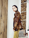 Pretty stylish woman in fashion dress with leopard print together in luxury rich room interior, lifestyle people concept