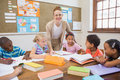 Pretty teacher helping pupils in classroom Royalty Free Stock Photo