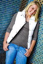 Pretty teen girl with blonde hair beautiful young teenage woman female wearing blue jeans and white vest standing against blue Stock Photos