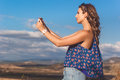 Pretty teen girl taking photo of nature by phone Royalty Free Stock Photo