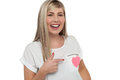 Pretty teen pointing towards pink paper heart Stock Photography