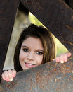 Pretty teen through rusty beams a beautiful peering the triangular frame of Royalty Free Stock Photography