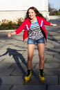 Pretty teenage girl rollerskating in park smiling Royalty Free Stock Images