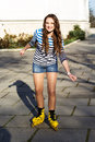 Pretty teenage girl rollerskating in park smiling Royalty Free Stock Photography