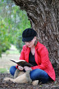 Pretty teenage girl studying holy bible beside huge tree in park Stock Photos