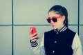 Pretty teenage girl in sunglasses using her smart phone Royalty Free Stock Photo