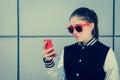 Pretty teenage girl in sunglasses using her smart phone Royalty Free Stock Photo