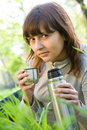 Pretty teenager girl drinking tea from thermos Stock Images