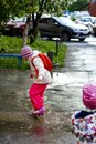 Pretty toddler girl wearing colorful raincoats and rain boots jumping in muddy puddles.