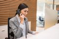 Pretty vietnamese receptionist talking on telephone at her workplace Royalty Free Stock Photos