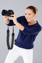 Pretty vivacious young female phoptographer smiling as she looks into the viewfinder on the back of her dslr camera on grey Royalty Free Stock Image