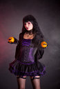 Pretty witch with halloween styled oranges in purple costume holding jack o lantern style Stock Photo