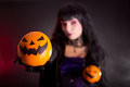 Pretty witch in purple halloween costume with jack lantern oranges selective focus on fruits Stock Photo