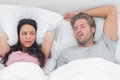 Pretty woman annoyed by the snoring of her husband women in bed Royalty Free Stock Photos