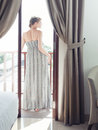 Pretty woman on a balcony in long dress standing Royalty Free Stock Photography