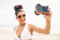 Pretty woman in bikini taking selfie at the beach Stock Photo
