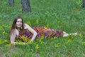 Pretty woman with bouquet of wild flowers young lying in the forest Stock Image