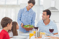 Pretty woman bringing a salad to her family women for the dinner Royalty Free Stock Image