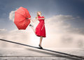 Pretty woman with a broken umbrella over the clouds standing on rope Royalty Free Stock Image