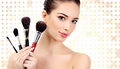 Pretty woman with cosmetic brushes against an abstract background circles and copyspace Stock Photos