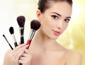 Pretty woman with cosmetic brushes against an abstract blurred background Stock Image