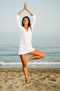 Pretty woman doing yoga on the beach portrait of a Stock Photos