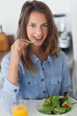 Pretty woman eating a salad with a glass of orange juice Royalty Free Stock Photo