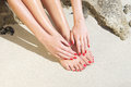 Pretty woman feet with red manicure and pedicure: relaxing on sand.