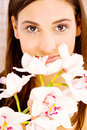 Pretty woman with flowers brunette behind white orchids Royalty Free Stock Image