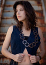 Pretty woman in fringed vest a portrait of a young a and large necklace with rusted steps behind her Stock Photos