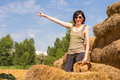 Pretty woman with hat standing in straw bales and pointing her finger toward the blue sky. Royalty Free Stock Photo
