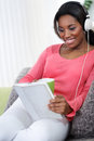 Pretty woman with headphones listening music african sitting on sofa tablet and Stock Photos