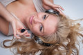 Pretty woman with headphones lying on her back wearing and a microphone smiling and looking to camera Royalty Free Stock Image