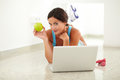 Pretty woman holding apple for wellbeing in sports clothing while surfing the web Royalty Free Stock Photo