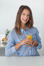 Pretty woman holding a glass of orange juice in the kitchen Royalty Free Stock Photography
