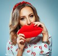 Pretty woman holding in hands big red lips, toy kiss-shaped Royalty Free Stock Photo