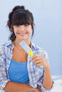 Pretty woman holding paint brush smiling at camera against a blue wall Stock Image