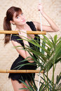 Pretty woman holds on bamboo rope ladder Royalty Free Stock Image