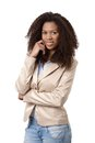 Pretty woman in jacket and jeans smiling afro american with hand on chin Royalty Free Stock Image