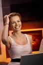 Pretty woman with laptop at home browsing internet by fireplace smiling happy hand in hair Stock Images
