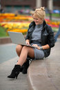 Pretty woman with laptop sitting in park Royalty Free Stock Photo